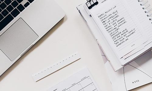 Cahier de prise de notes et ordinateur.