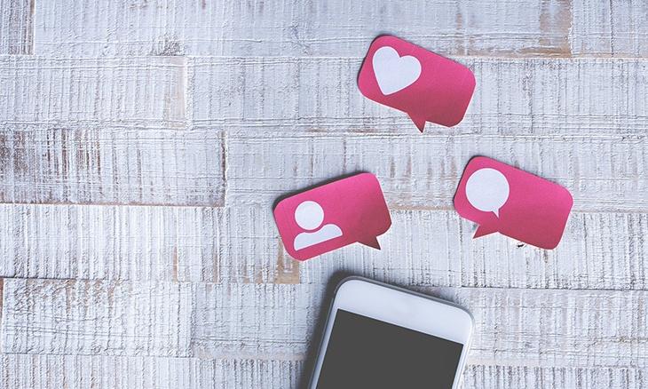 Photo d'un smartphone et d'exemples de réaction sur les réseaux sociaux (Like, Commentaire, Partage) sur une table.