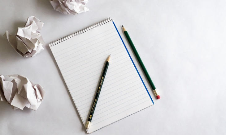 Photo d'un carnet de notes posé sur une table avec des crayons à papier.Feuille blanche, crayons et feuilles chiffonnées lors de l'écriture d'un article de blog.