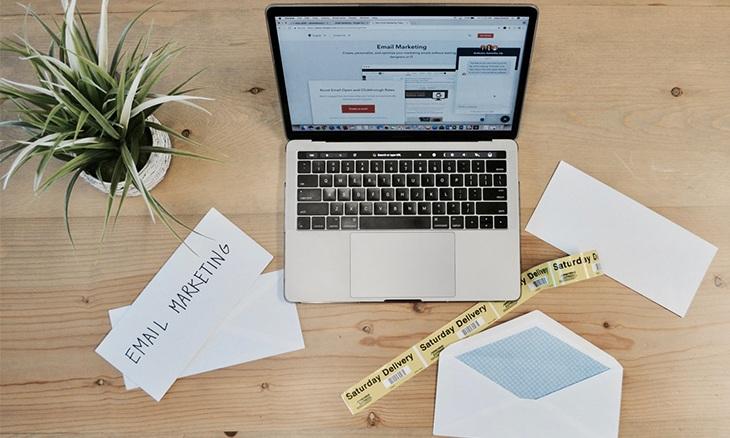 Un ordinateur posé sur une table sur laquelle sont disposées des feuilles de papier et des enveloppes.