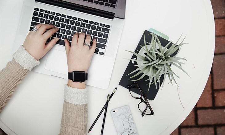 Mains d'une femme écrivant sur son clavier d'ordinateur.