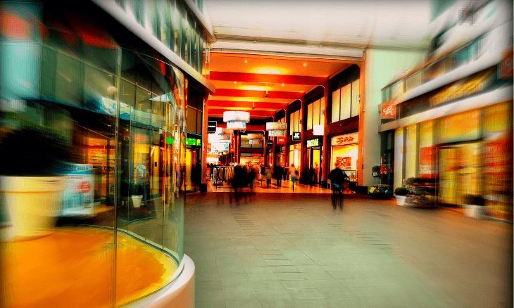 Photo avec effet dynamique d'une galerie marchande avec des commerces de détail.